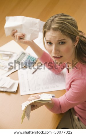 A young woman looks upset while sorting through her old receipts.  Vertical shot. - stock photo