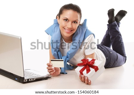 A young woman lying on the floor with a laptop, holding a credit card and a gift box