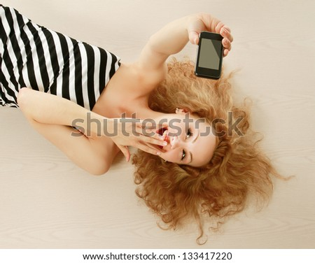 A young woman lying on the floor with a mobile phone - stock photo