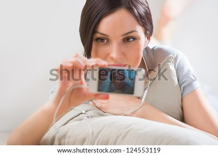 A young woman lying on the floor with her phone and shooting ( photographs ) herself using built-in camera