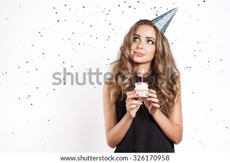 A young woman makes a wish with cake - stock photo