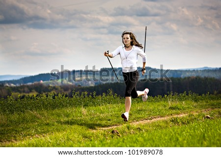 a young woman making nordic walking. outdoor shoot. - stock photo