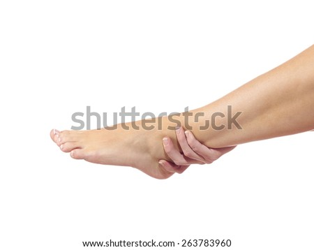 A young woman massaging her painful ankle. Medical concept - stock photo