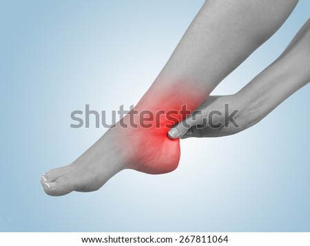 A young woman massaging her painful ankle. Medicine concept photo. - stock photo