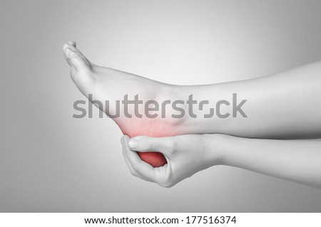 A young woman massaging her painful heel - stock photo