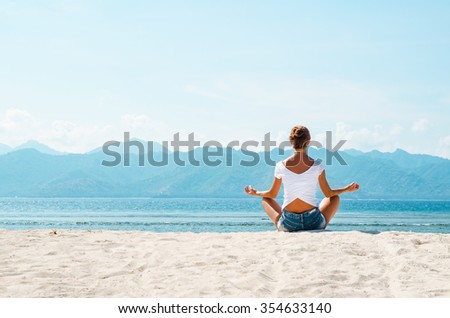 A young woman meditates in a pose of yoga on a sandy beach overlooking the blue ocean and the mountains. Stock image. - stock photo