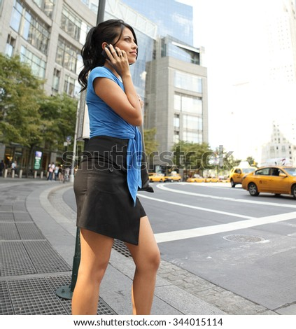 A young woman on her cell phone while waiting for a bus at a bus stop.