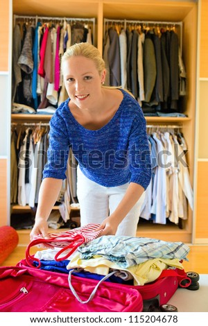 a young woman packs her suitcase for the journey to your holiday. - stock photo