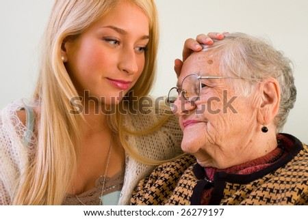 A young woman patting an older one whit love and empathy - part of a series.
