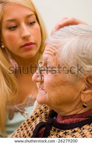 A young woman patting an older one whit trust and empathy (focus on the old woman) - part of a series. - stock photo