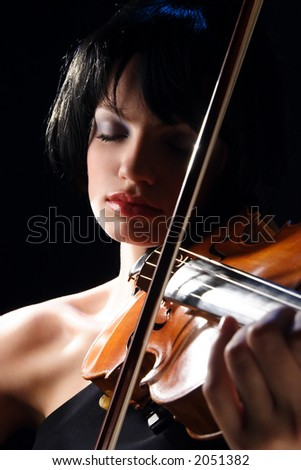 A young woman playing her violin with expression.