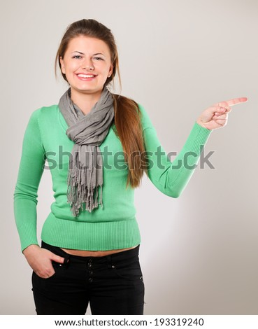 A young woman pointing at something, isolated on grey background - stock photo