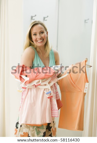 A young woman poses with clothing she has picked out in a store.  Vertical shot.