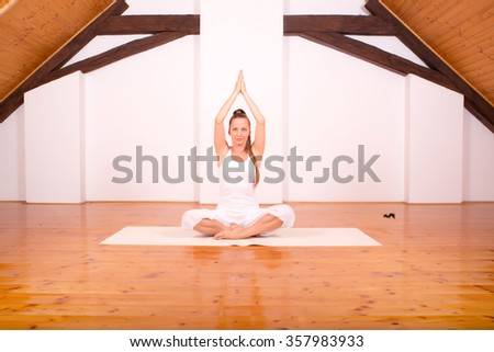 A young Woman practicing Yoga in a attic Studio.