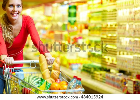 A young woman pulling a shopping trolley with foodstuff along the grocery, looking at camera and smiling