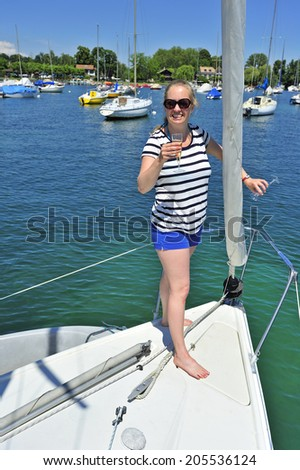 A young woman raises a glass in toast at the bow of a yacht - stock photo