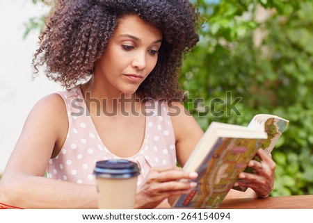 A young woman reading a book while drinking coffee outside - stock photo