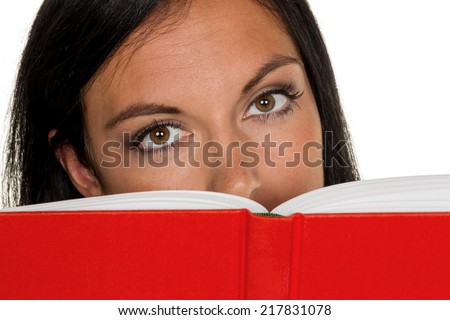 a young woman reading a book with a red envelope - stock photo