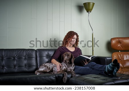a young woman reading with her dog  - stock photo
