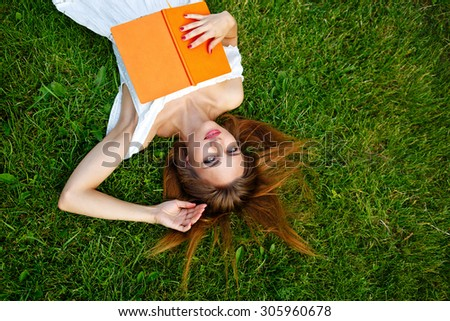 A young woman relaxes with a book lying on a green lawn in the park. Summer day. Soft focus - stock photo