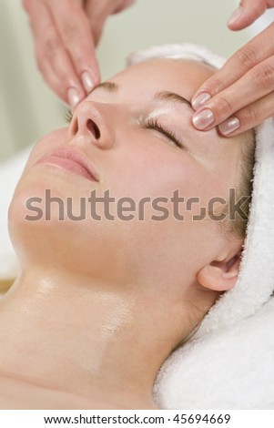 A young woman relaxing at a health and beauty spa while having a head massage or facial treatment
