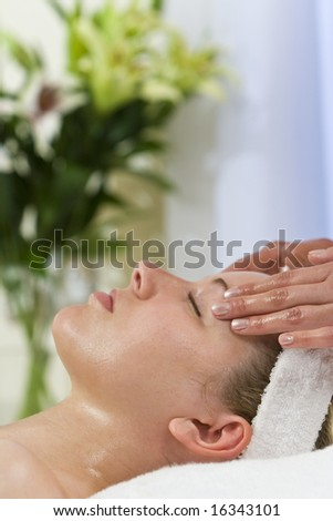 A young woman relaxing at a health spa while having a facial treatment - stock photo