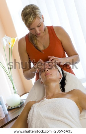 A young woman relaxing at a health spa while having a facial treatment.