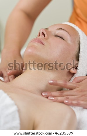 A young woman relaxing at a health spa while having a facial treatment or relaxing massage