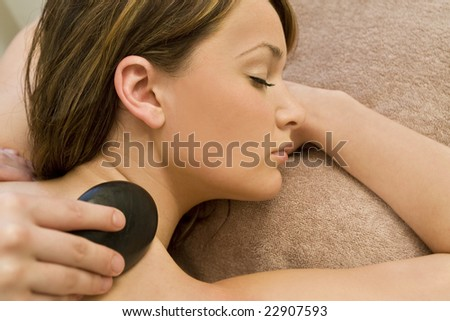 A young woman relaxing at a health spa while having a hot stone massage