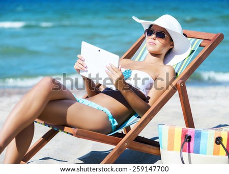 A young woman relaxing with a tablet computer on a beautiful beach - stock photo