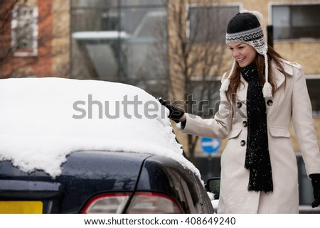 A young woman removing snow from a car