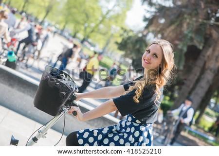 A young woman rides a bicycle in city park.Sunny summer day.Healthy lifestyle.Active people. Outdoors - stock photo