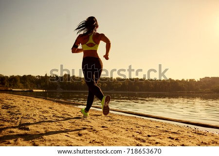 A young woman runner runs at sunset in a park in the park by the lake.