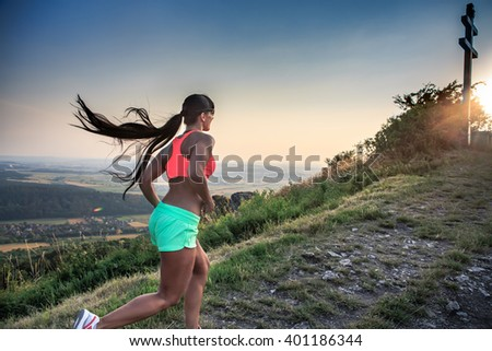 a young woman running in the mountains - stock photo