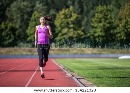 A young woman running on a sports track.