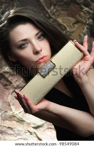 a young woman's face with beautiful makeup and handbag - stock photo