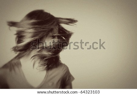 A young woman shaking her head with her hair flying around her. Image is done in a vintage style - blurriness and grain should be expected. - stock photo