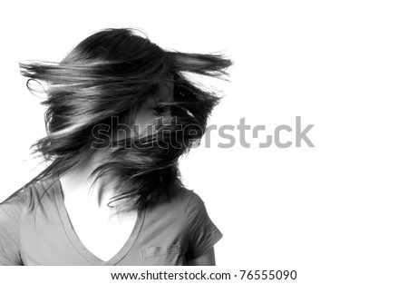 A young woman shaking her head with her hair flying around her in black and white.