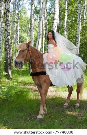 a young woman sits astride a horse in a wedding dress