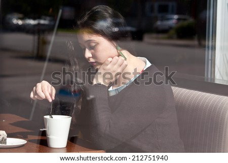 A young woman sits in a cafe stirring her tea and looking sad. - stock photo