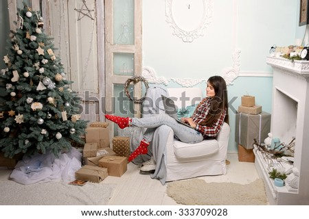 a young woman sitting in a chair in a Christmas interior, near the fireplace, Christmas tree, looking at laptop, ischit presents, works - stock photo