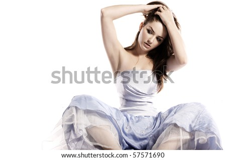 A young woman sitting in a glamorous dress fixing her hair. - stock photo