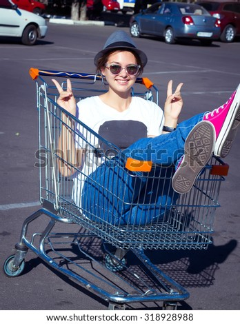 A young woman sitting in a large shopping cart and shouting for joy with her hands up in the air.Girl sitting in shopping cart - stock photo