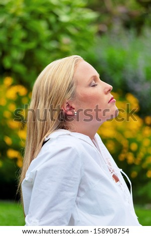 a young woman sitting in a meadow, enjoying the quiet. - stock photo