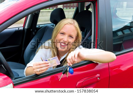 a young woman sitting in her car and proudly shows her license after passing the driving test. - stock photo