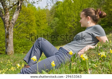 A young woman sitting in the green grass between flowers. - stock photo