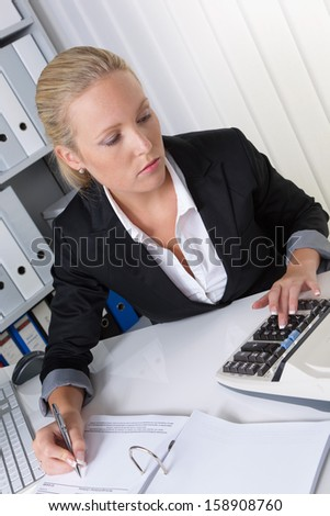 a young woman sitting in the office and credited to the calculator - stock photo