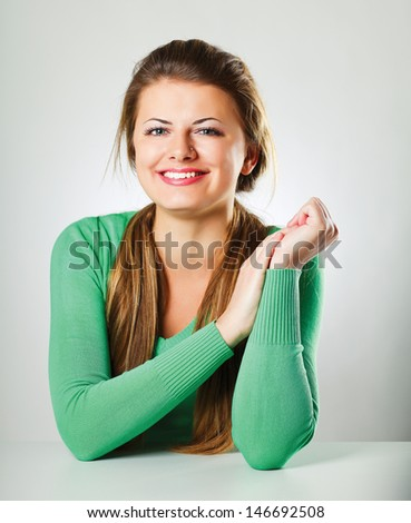 A young woman sitting isolated on grey background