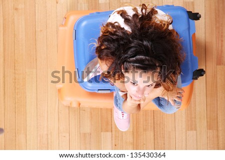 A young woman sitting on a stack of suitcases. - stock photo