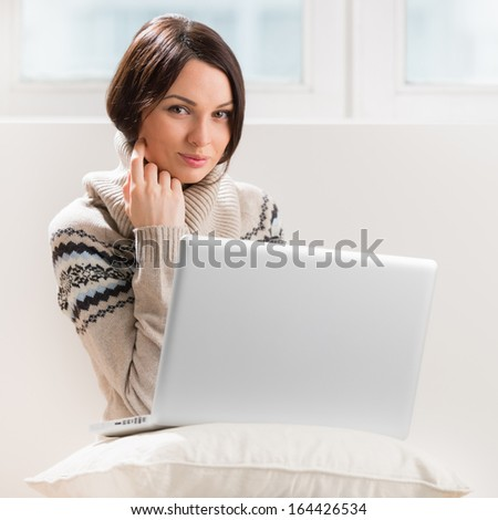 A young woman sitting on the floor in front of her laptop, looking at camera - stock photo